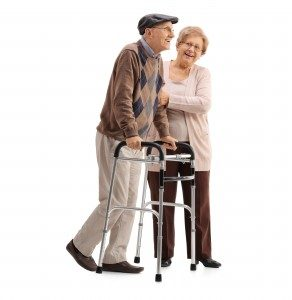 Full length portrait of a mature woman helping a mature man with a walker isolated on white background